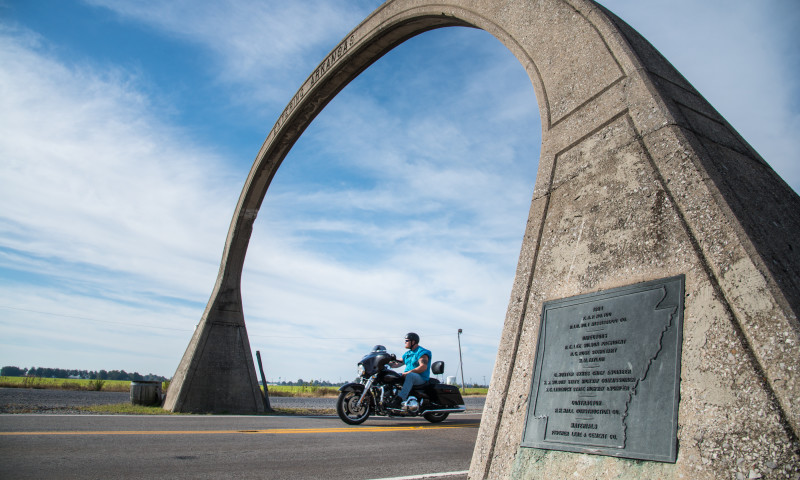 A guy on a motorcyle riding under the US Hwy 61 Arch.