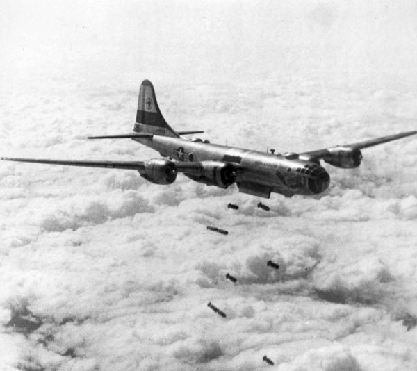United State Air Force Bomber Plane dropping bombs above the clouds.